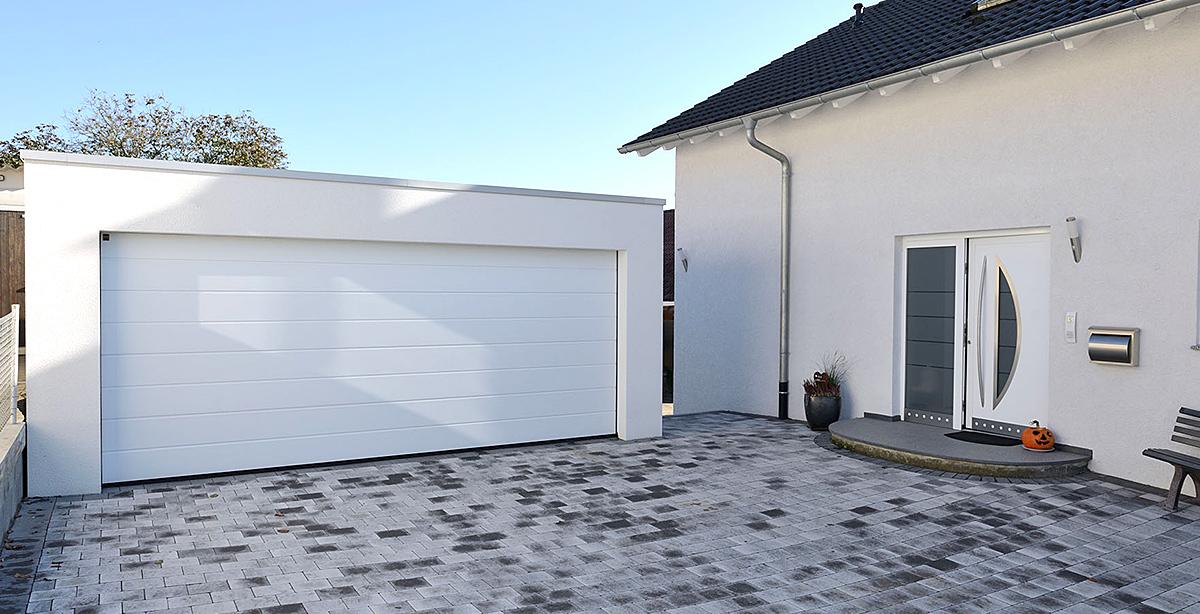 Doppelgarage mit weißem Tor neben Haus